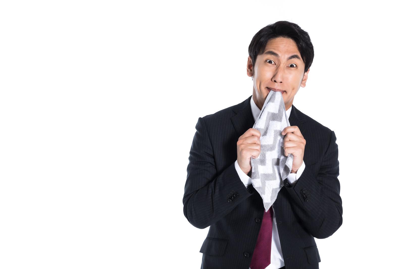 「悔しくてハンカチを噛む男性」の写真[モデル:大川竜弥]