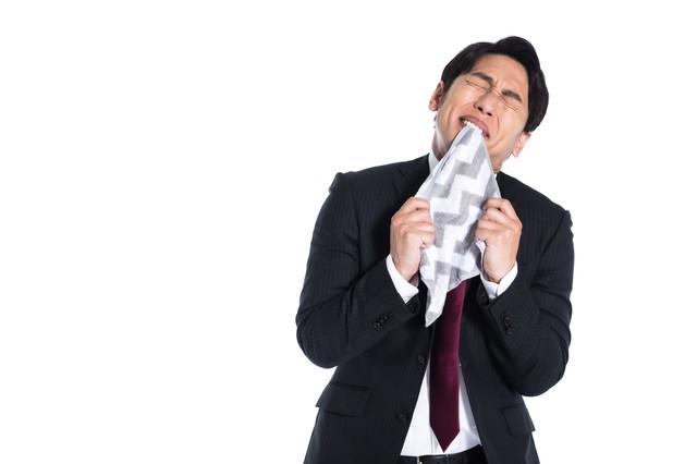 マンガなどで悔しい思いをしてハンカチを噛んでいるシーンの写真
