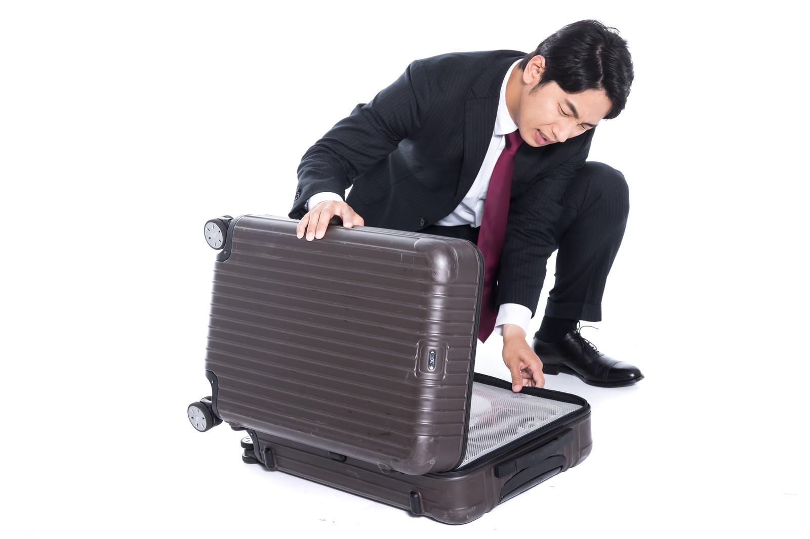 「スーツケースが閉まらないトラブルの会社員」の写真[モデル:大川竜弥]