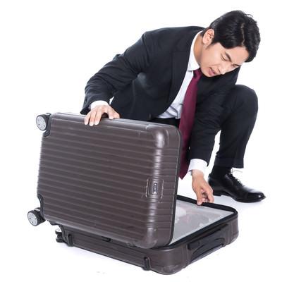 スーツケースが閉まらないトラブルの会社員の写真