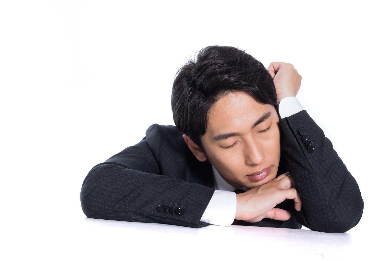 「肘を立てて昼寝する会社員」の写真[モデル:大川竜弥]