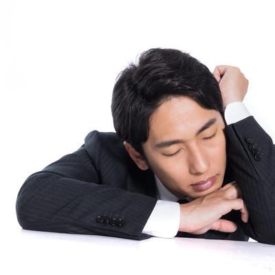 肘を立てて昼寝する会社員の写真