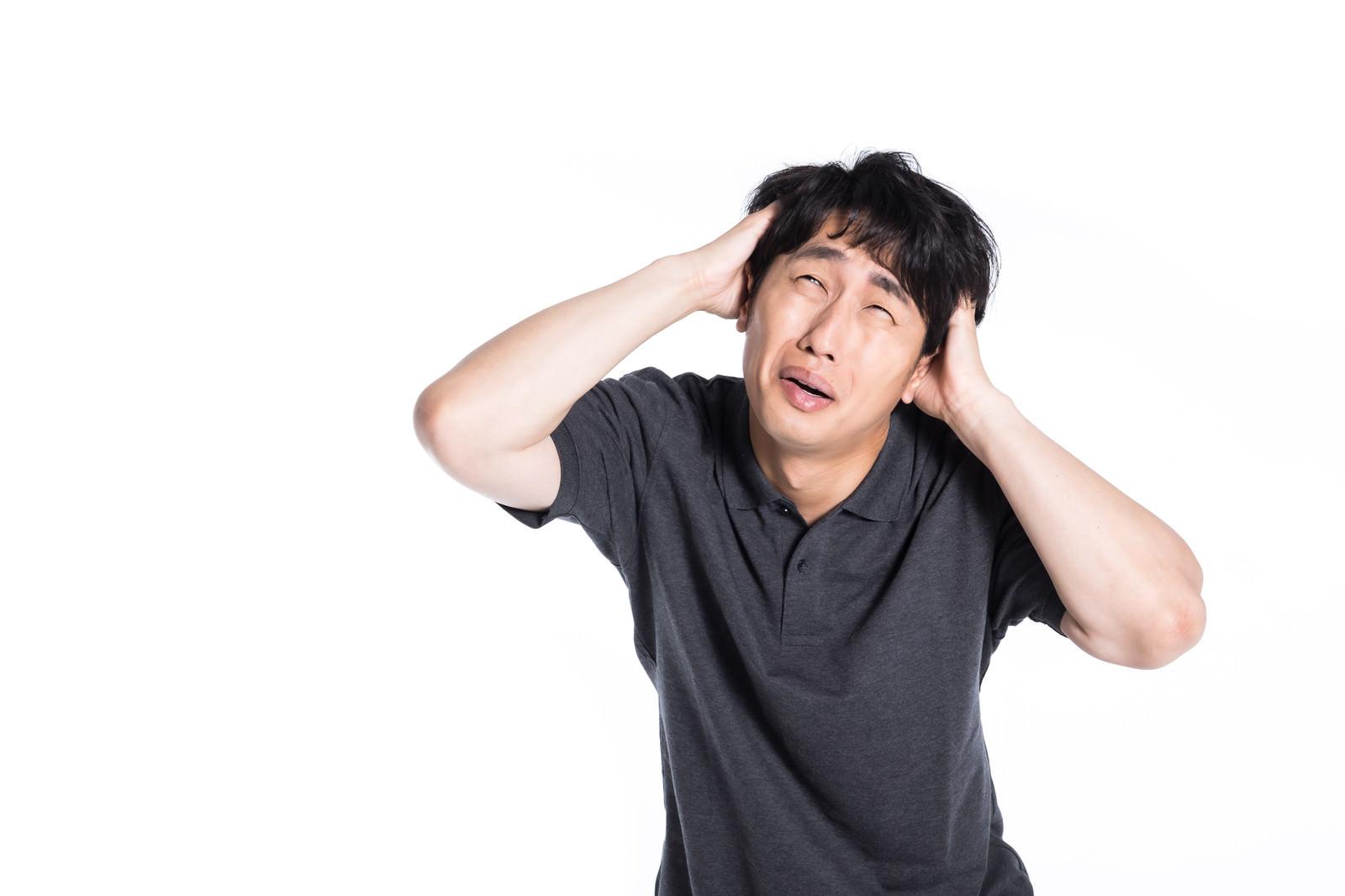 「頭を抱えて焦る男性」の写真[モデル:大川竜弥]