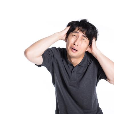 頭を抱えて焦る男性の写真