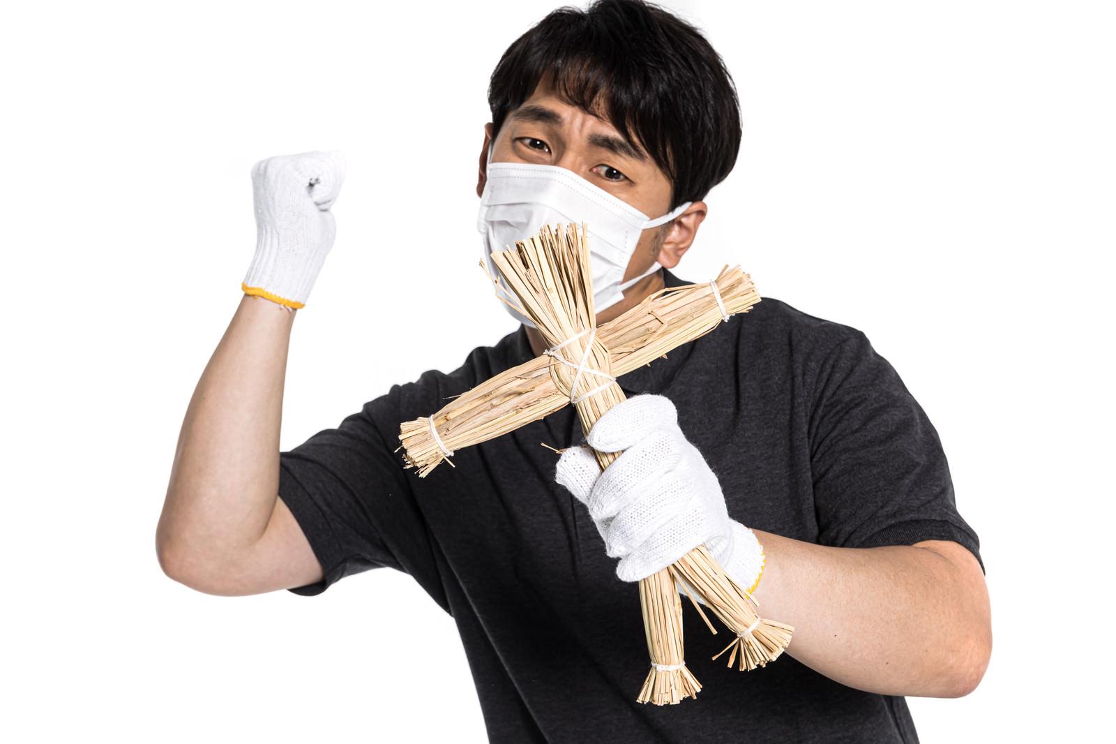 「正体を明かさず藁人形に恨みを込める男性」の写真[モデル:大川竜弥]