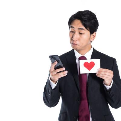 スマートフォンに心拍数のログを残す男性の写真