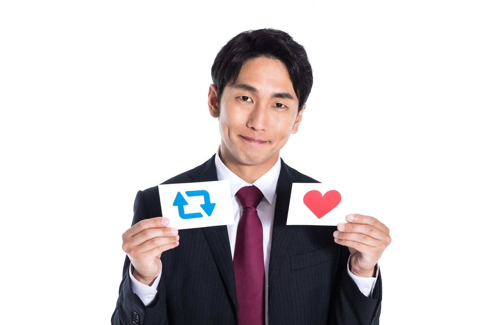 「リツイートといいねマークを持つビジネスマン」の写真[モデル:大川竜弥]