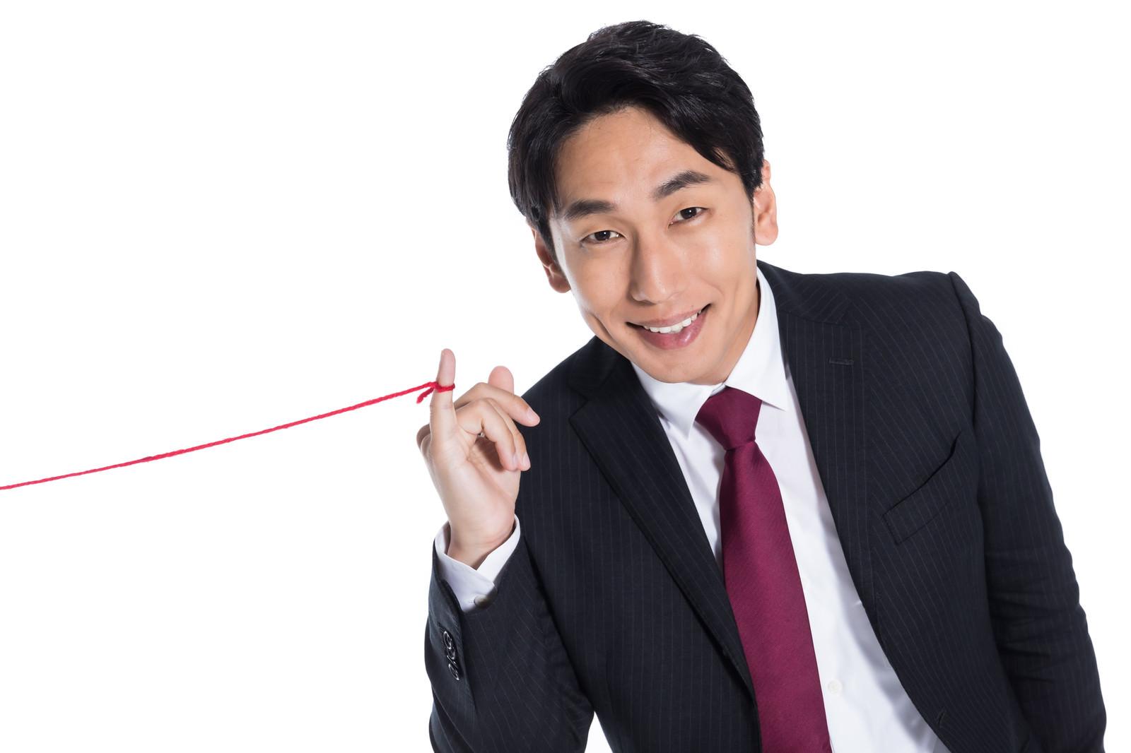 「運命の赤い糸を見せびらかす男性」の写真[モデル:大川竜弥]
