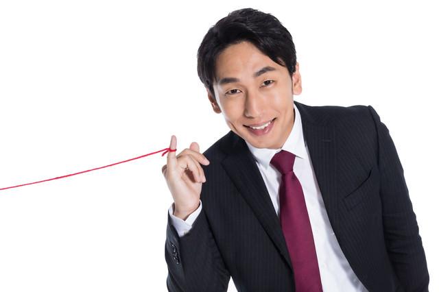 運命の赤い糸を見せびらかす男性の写真