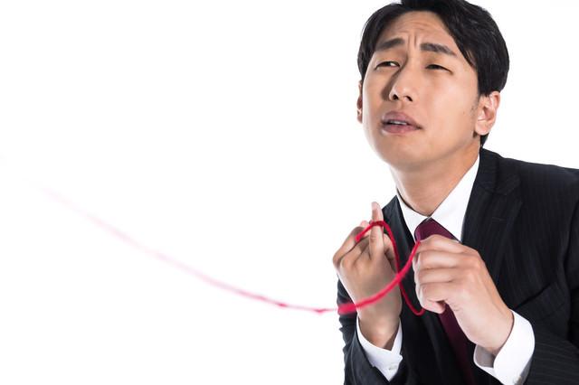 赤い糸を手繰り寄せる独身男性の写真