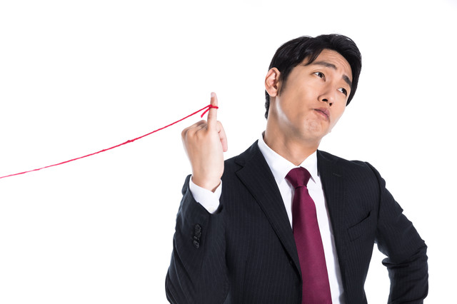 片想いの赤い糸に気付かない会社員の写真