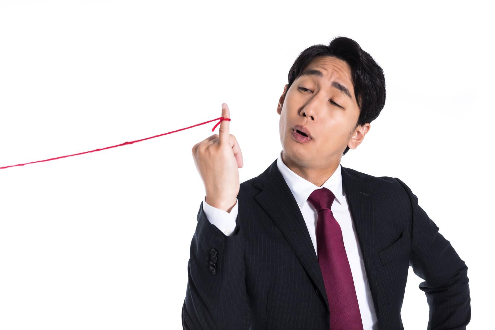 「小指に赤い糸が結ばれている事に気が付く会社員」の写真[モデル:大川竜弥]