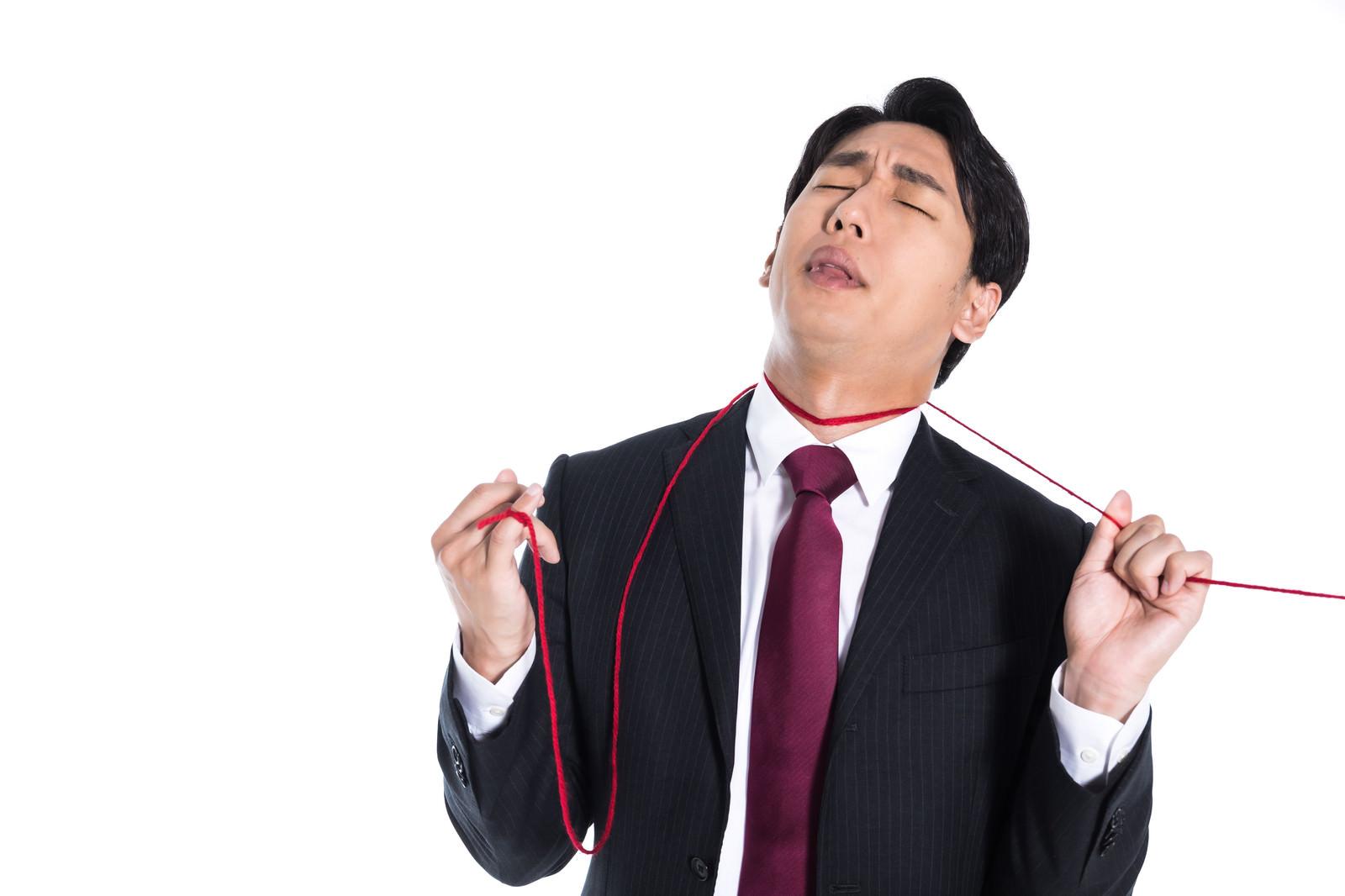 「運命の赤い糸が首に巻き付き苦しむ男性」の写真[モデル:大川竜弥]