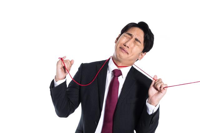 赤い糸に運命を握られる男性の写真