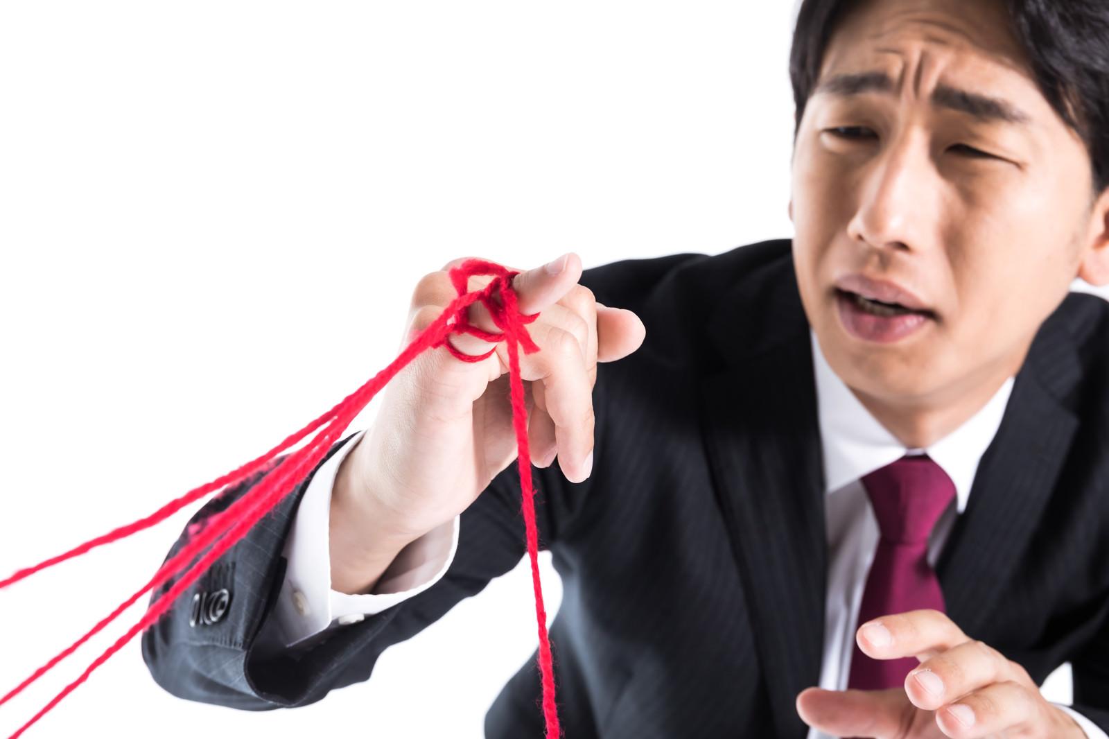 「たくさんの運命の赤い糸に困惑する男性」の写真[モデル:大川竜弥]