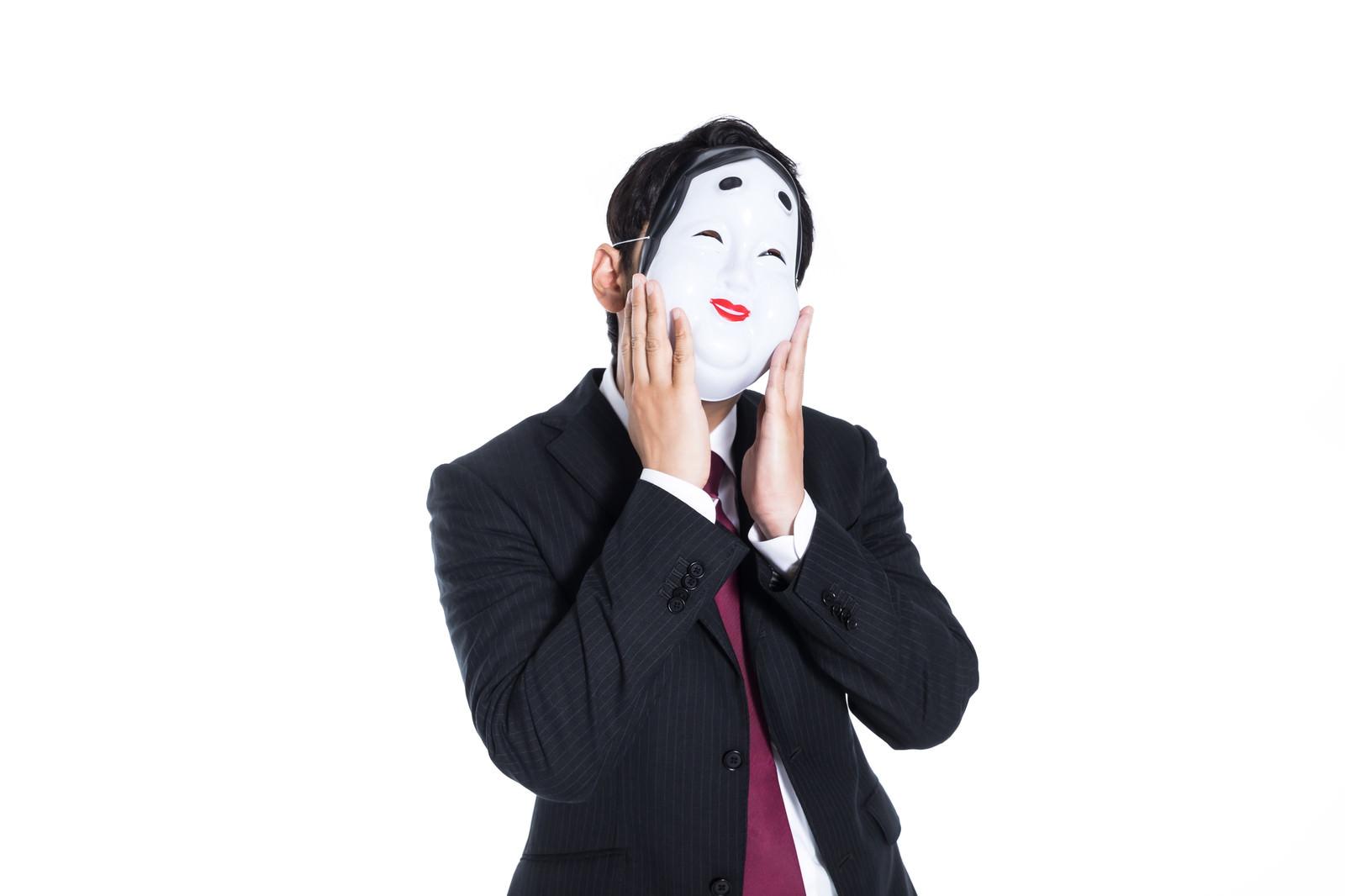 「表面上はニコニコしているスーツ姿の男性」の写真[モデル:大川竜弥]