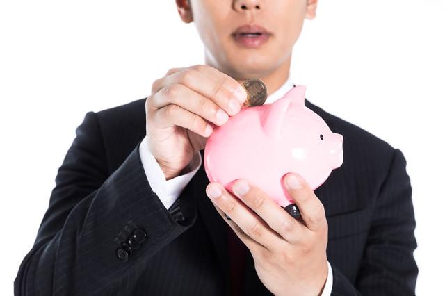 お小遣いの残りを貯金する男性の写真