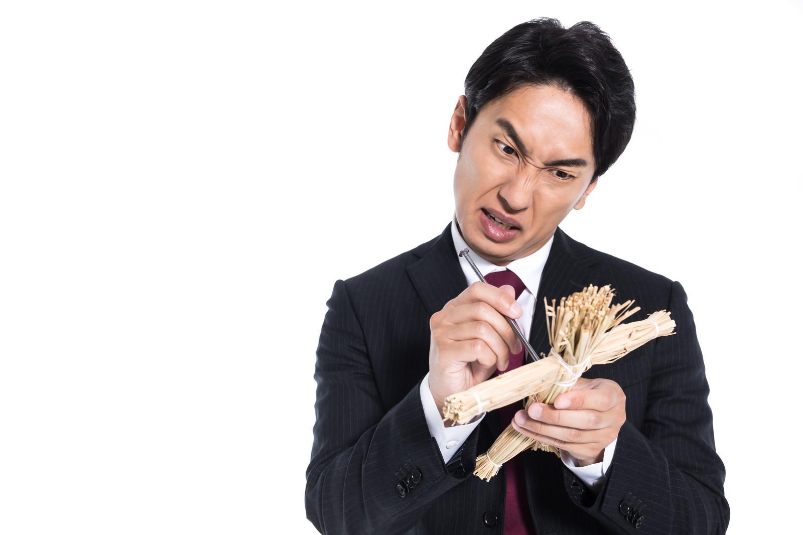 「藁人形に五寸釘を刺すサラリーマン」の写真[モデル:大川竜弥]