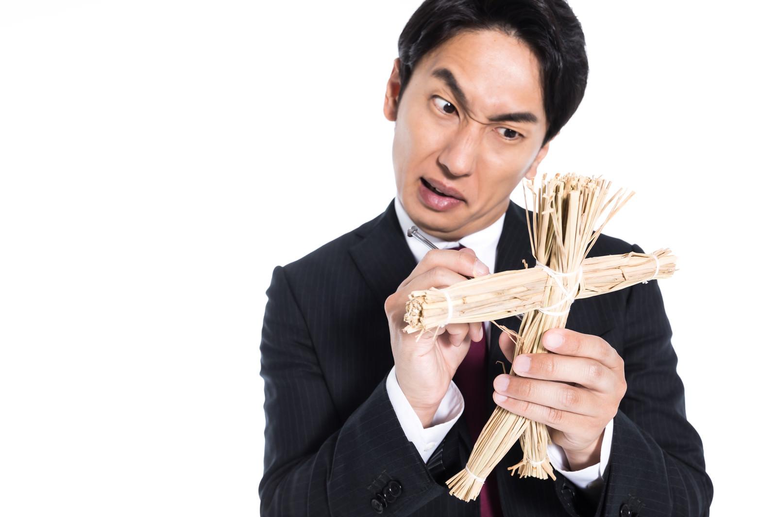 「藁人形の使い方をレクチャーする呪師」の写真[モデル:大川竜弥]