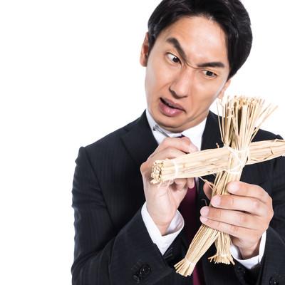 藁人形の使い方をレクチャーする呪師の写真