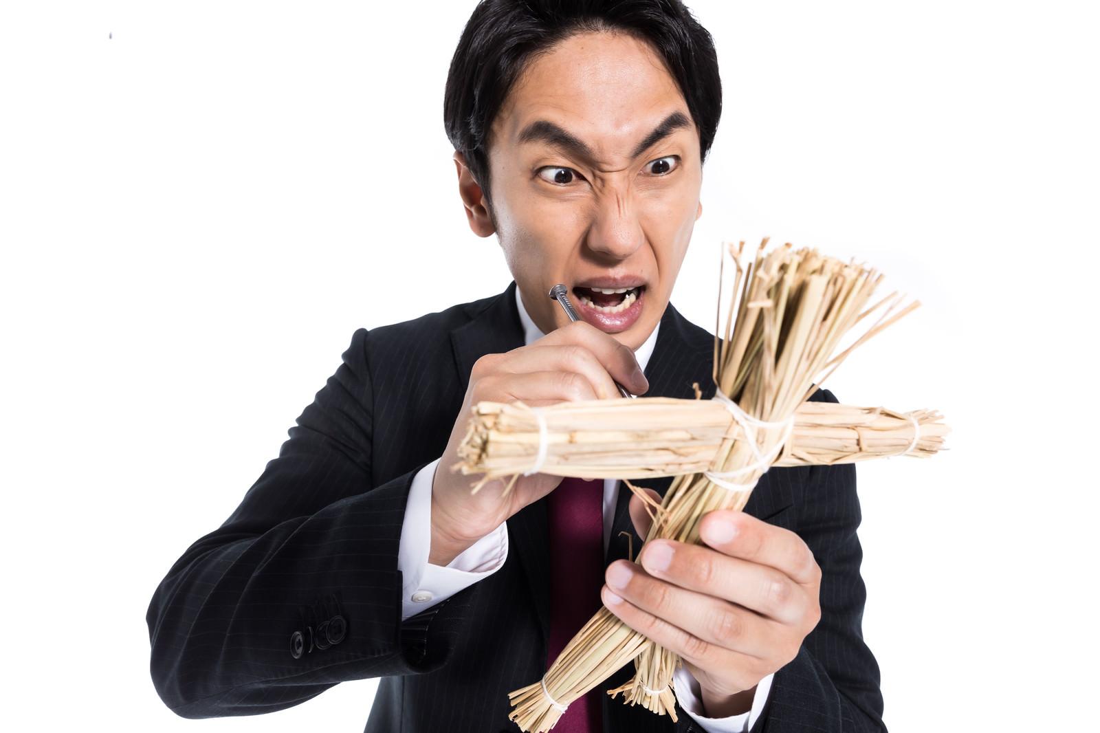 「嫌いな人間を藁人形に見立てて呪う会社員」の写真[モデル:大川竜弥]
