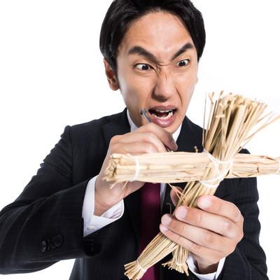 嫌いな人間を藁人形に見立てて呪う会社員の写真