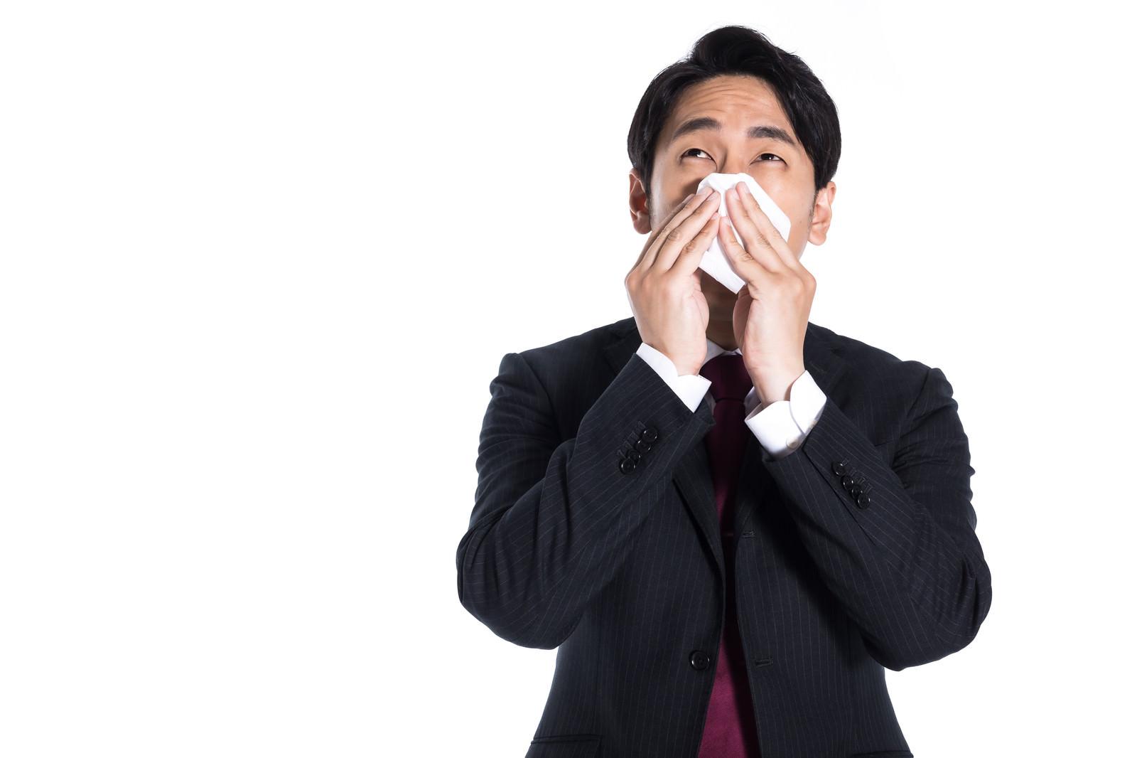 「花粉症で鼻を押さえる会社員」の写真[モデル:大川竜弥]