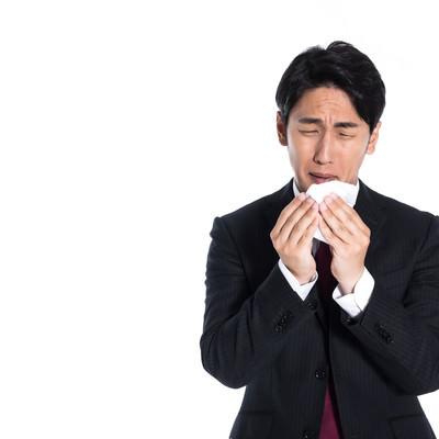 花粉症で目がショボショボする男性会社員の写真