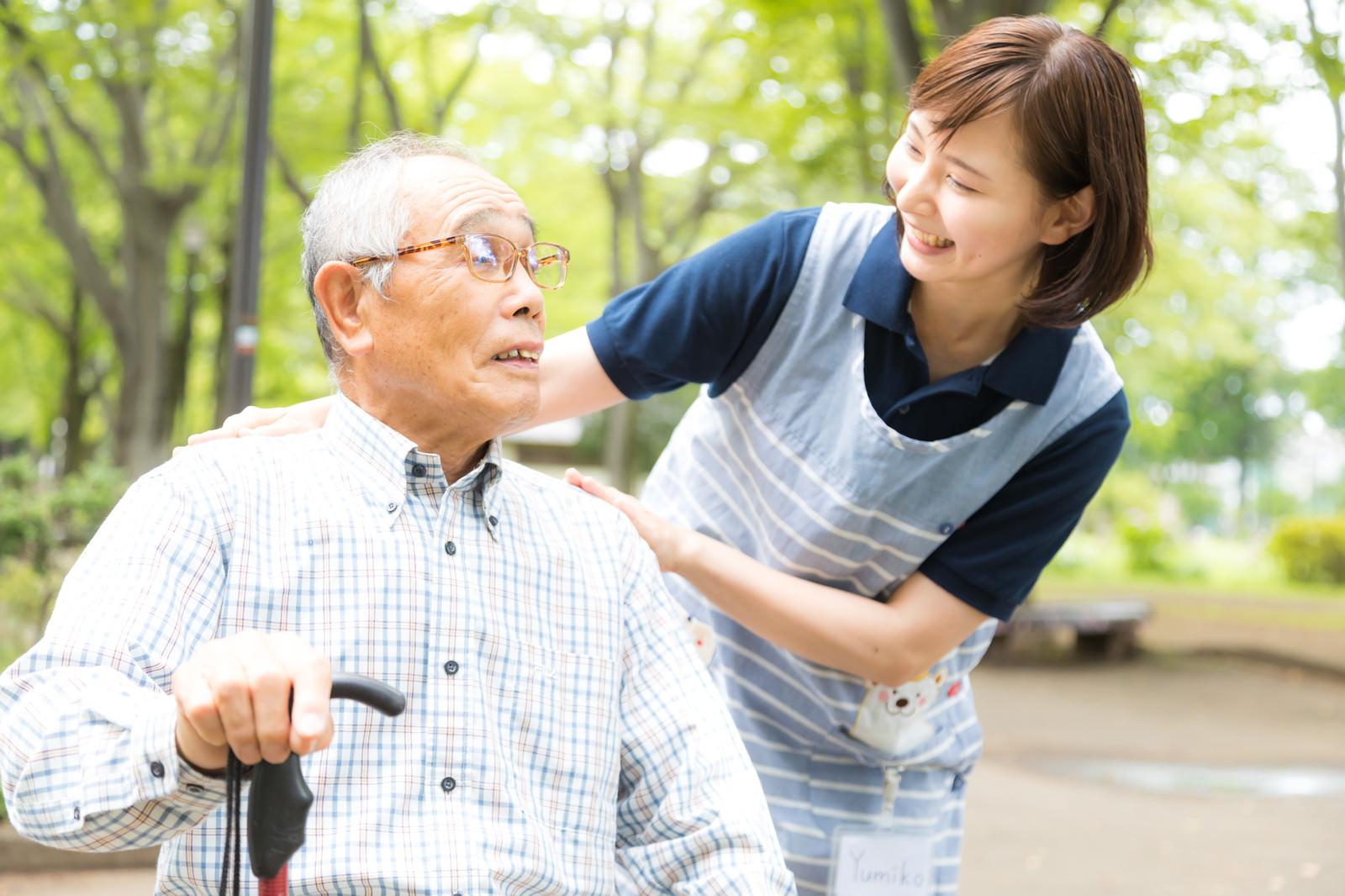 「お爺さんに笑顔で挨拶する女性の介護士」の写真[モデル:yumiko まーちゃん]