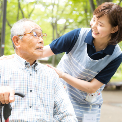 お爺さんに笑顔で挨拶する女性の介護士の写真