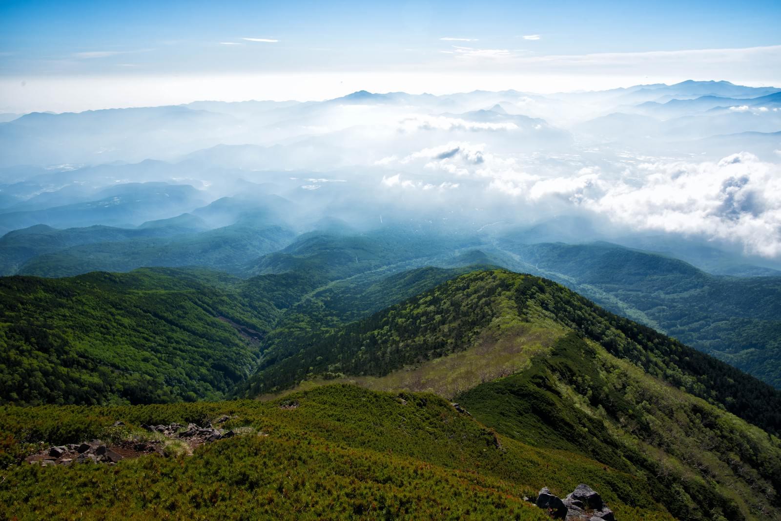 「雲に浮かび上がる杣添尾根と清里高原」の写真