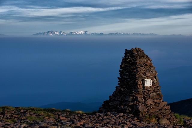 硫黄岳のケルンと遥かに望む北アルプスの写真