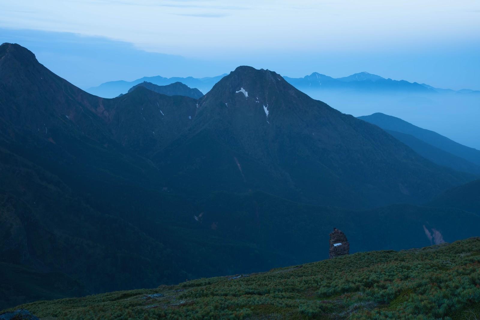 「硫黄岳のケルンと霞がかる阿弥陀岳」の写真