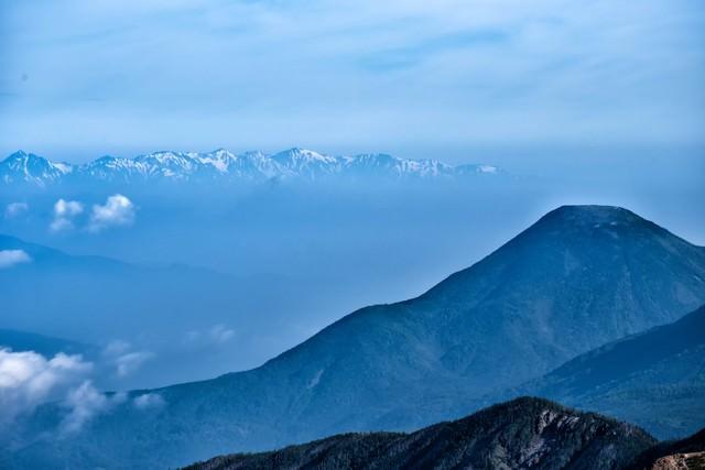 霞ゆく蓼科山と後立山連峰の写真