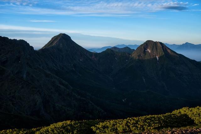 日に照らされた深い渓谷を有する山の写真