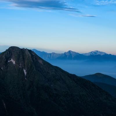 阿弥陀岳と霞がかる南アルプスの写真