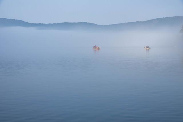 霧の芦ノ湖に浮かぶ釣り船の写真