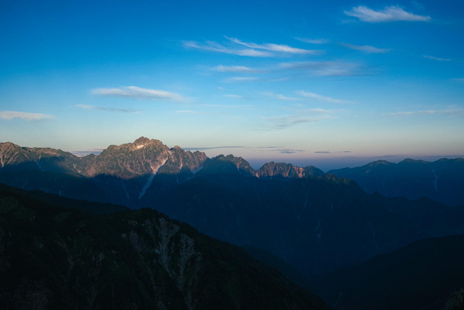 「朝日を迎える山頂部分と影」の写真