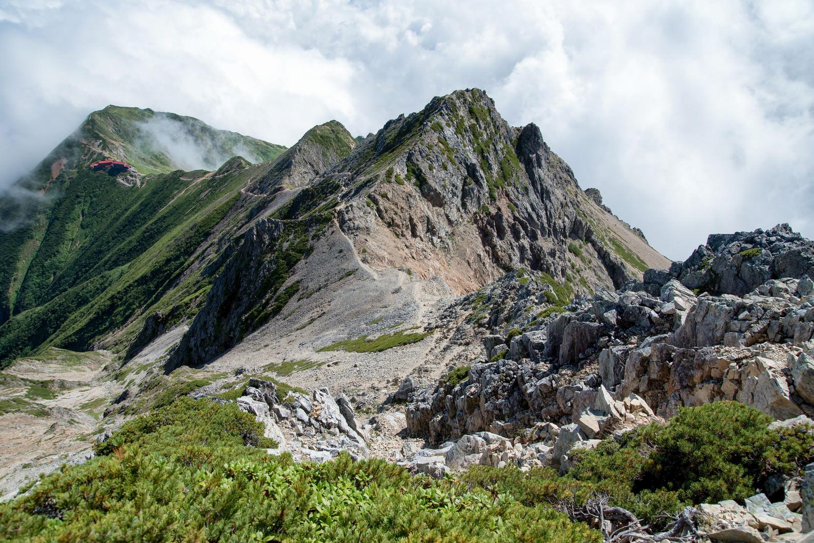岩場の登山道を抜けた先にある山小屋のフリー素材