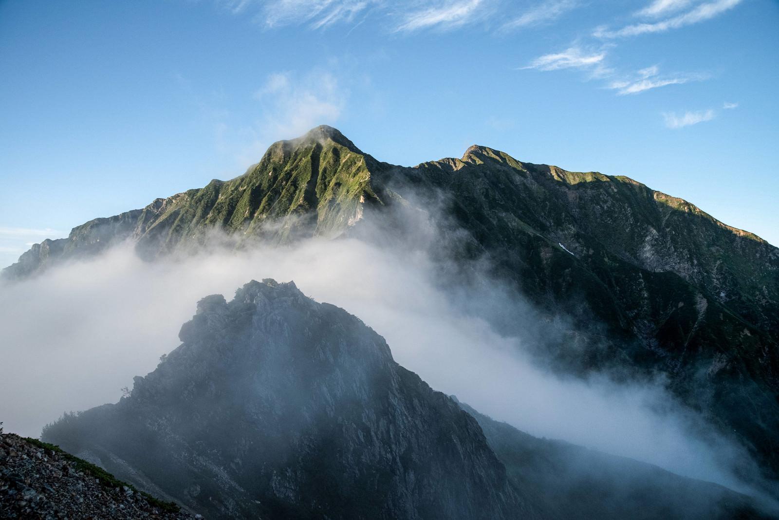 「雲に隠れた岩稜と聳える稜線」の写真