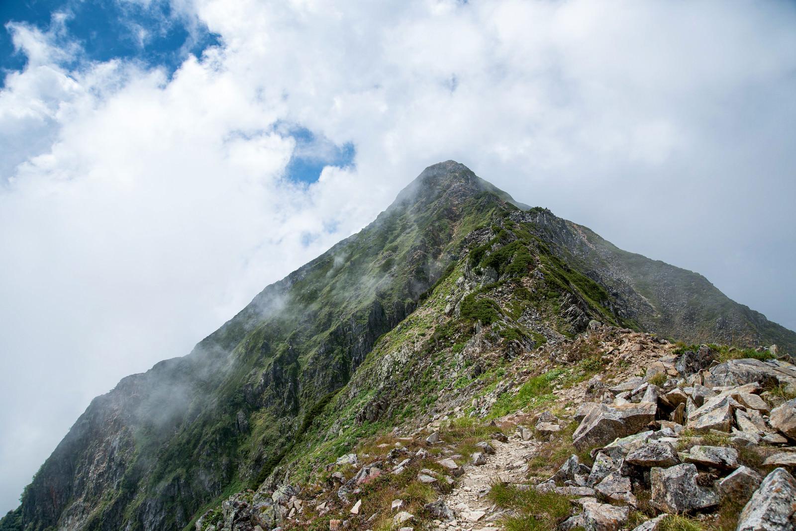 「雲かかる山頂へと続く登山道」の写真