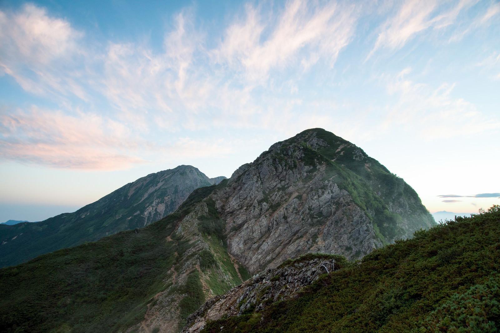 「夕焼け色に染まる岩稜と登山道」の写真
