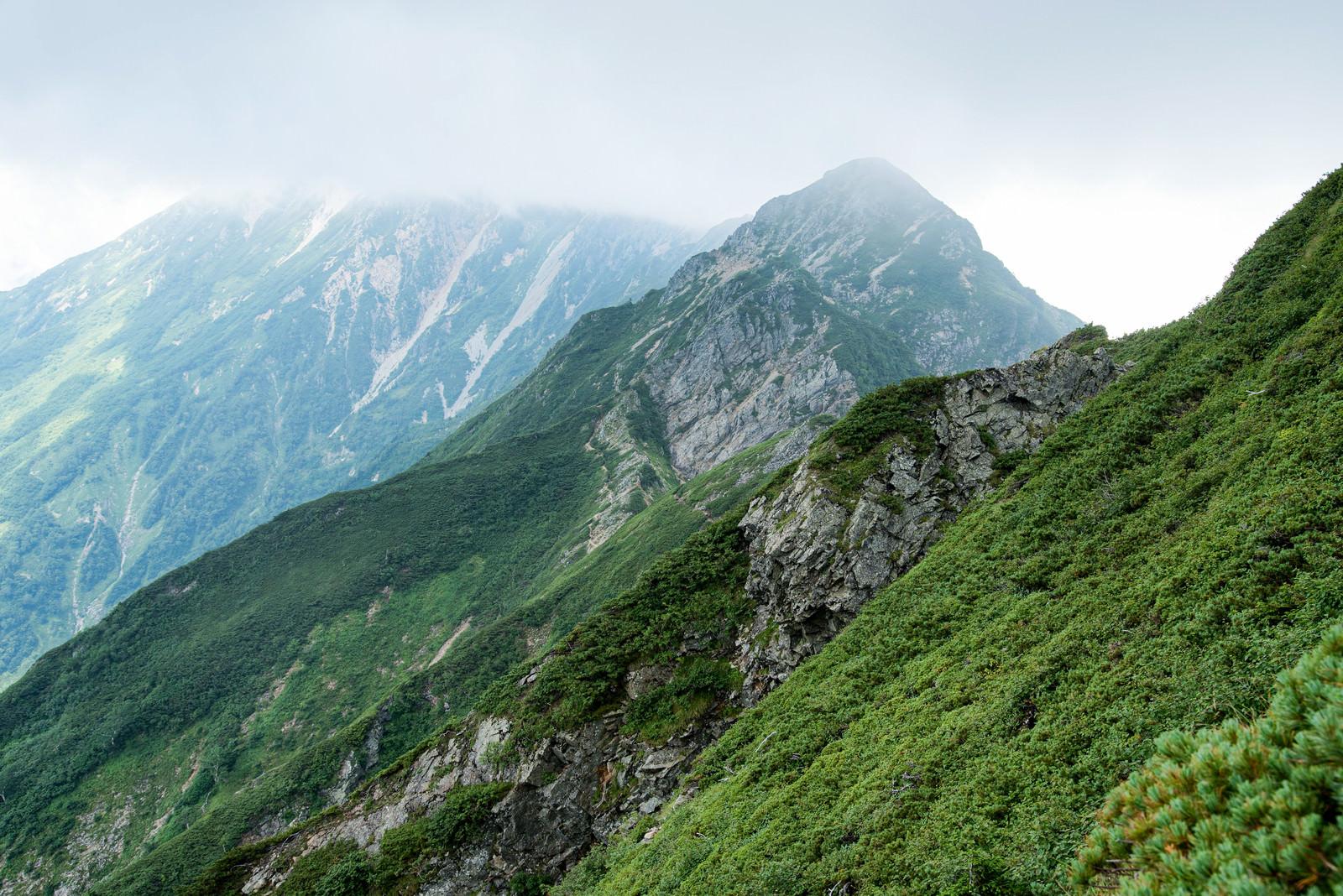 「雲で隠れた岩尾根と切り立つ山々」の写真