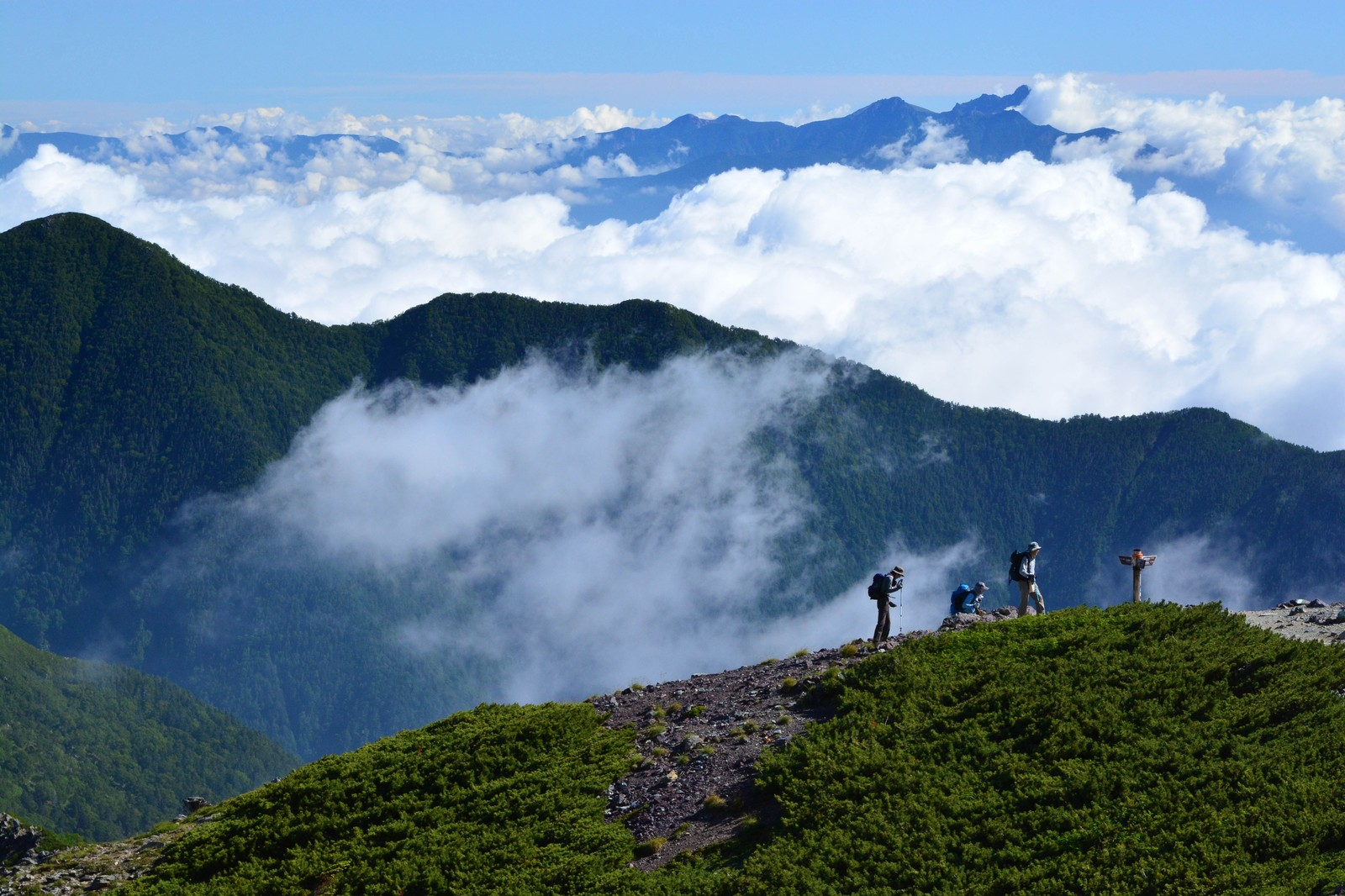 「山間の雲と登山道を歩く人」の写真