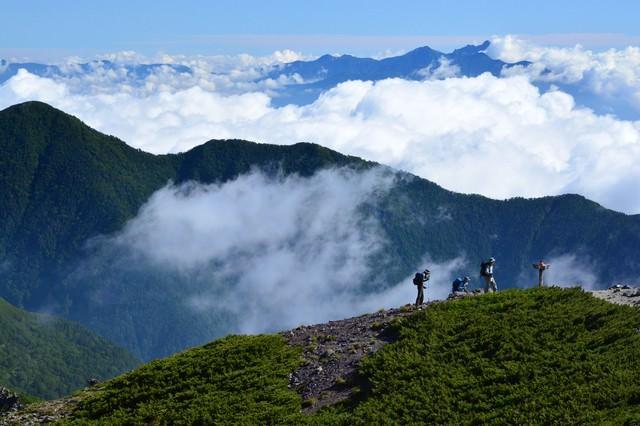 山間の雲と登山道を歩く人の写真