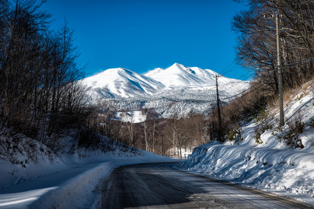 乗鞍岳へと続く残雪の道路の写真