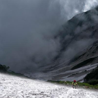 大雪渓をよじ登る登山者の写真
