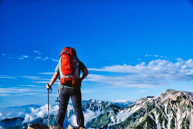 登頂して眼下を眺める登山者の男性の写真