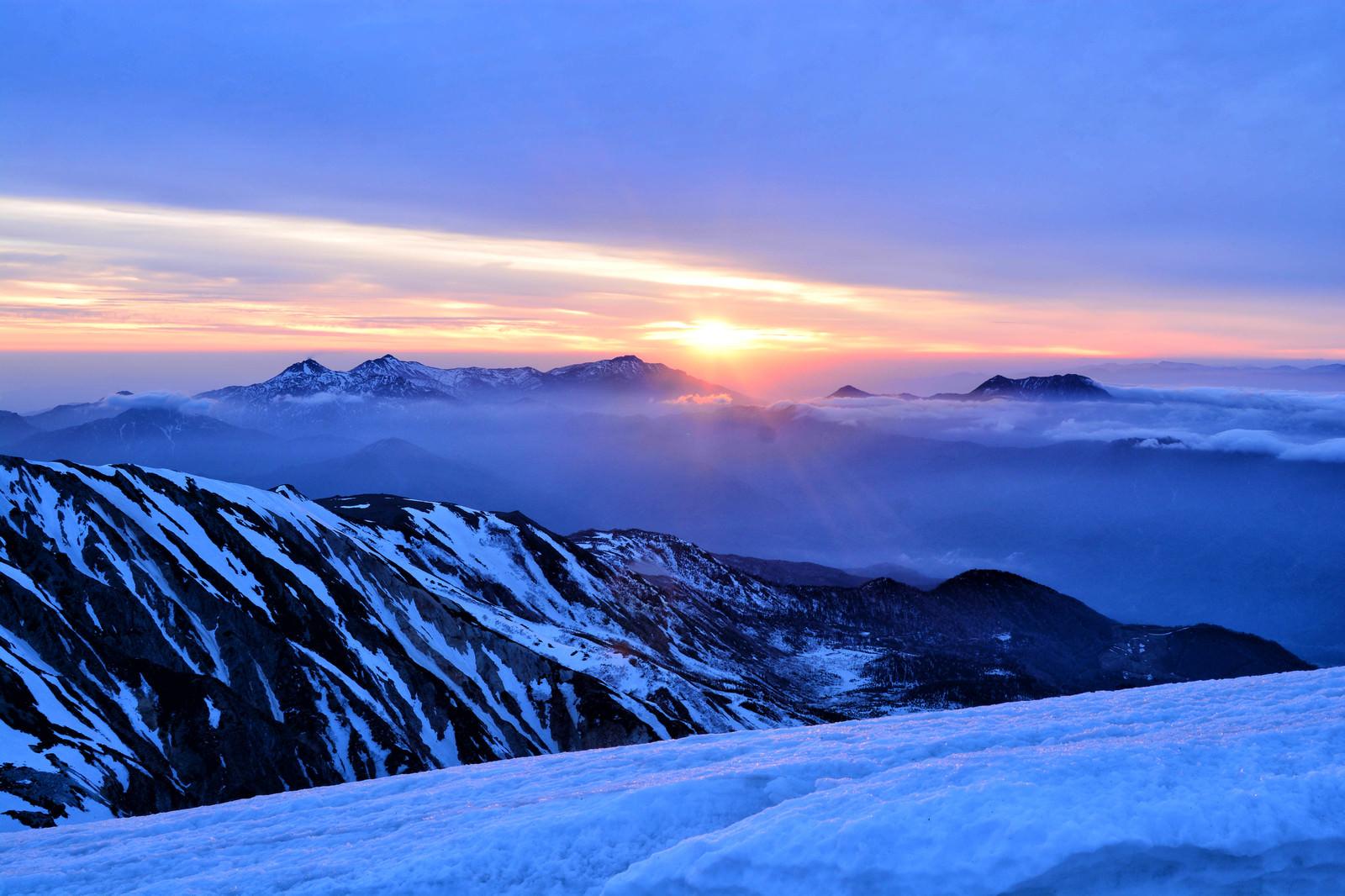 「雪山から拝む日の出」の写真