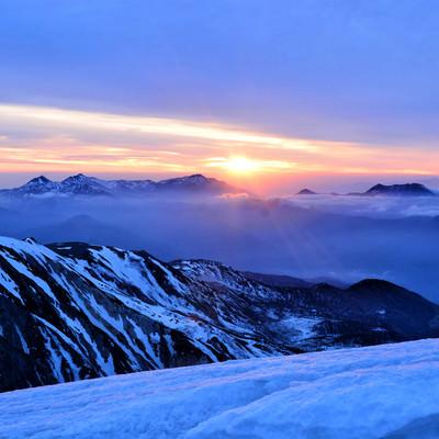 雪山から拝む日の出の写真